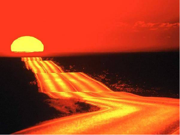 sunset shinning red on a desert road